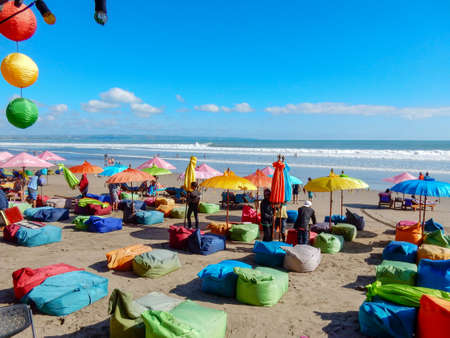 Seminyak Beach, Bali, Indonesia - May 24, 2016: Multicolored beach umbrellas and soft chairs on the beach against the background of the sea and waves. White fluffy clouds in the blue sky. Preparing for the sunset