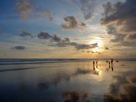 Legian Beach, Bali, Indonesia - May 22, 2016: mirror beach at sunset with reflection of clouds in the wet sand. People on the horizon. Picturesque sky