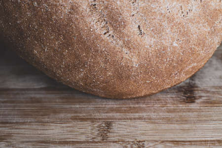 A piece of large round freshly baked whole grain bread on a wooden surface. Crust. Bakery, food concept. Country style. Closeup Фото со стока