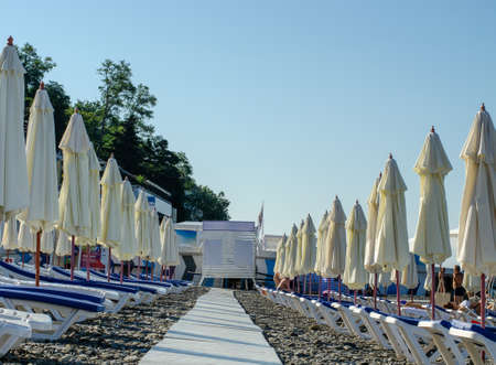 Sochi, Russia - July 20, 2019: A wooden walkway stretching into the distance, between folded beach umbrellas and sun beds. Beach in the morning
