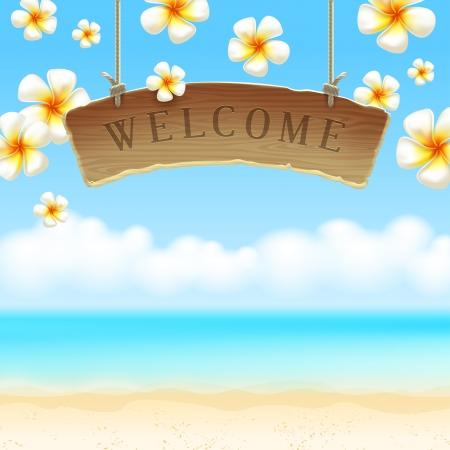 bienvenida: El letrero de bienvenida de madera cuelga en contra de flores tropicales y la orilla del mar