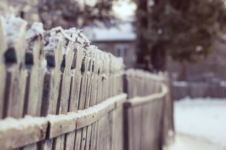snowcovered: Snow-covered old rural wooden fence.