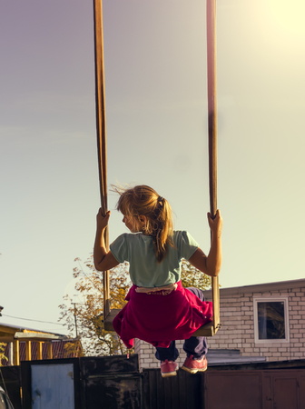 Young  girl on swing in the garden