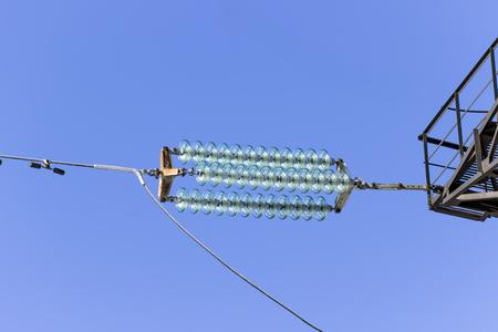 torres de alta tension: altas torres de energía de voltaje contra el cielo azul y los rayos del sol