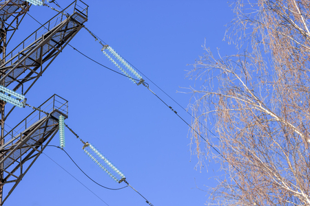 energy needs: high voltage power pylons against blue sky and sun rays