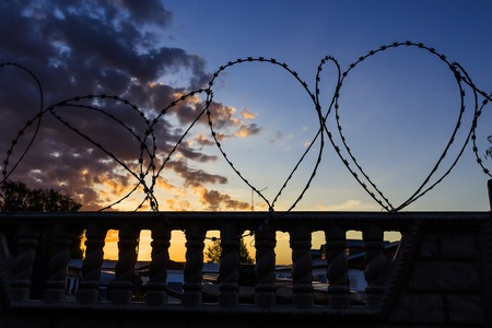 keepout: barbed wire against evening sky