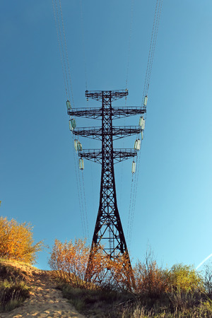 High voltage tower on a background of blue sky in autumn. Stock Photo