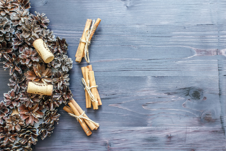 Cinnamon sticks and cork from wine on a wooden background