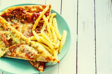 Pizza on a blue plate on a white wooden background. Retro style