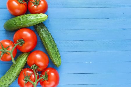 Fresh cucumbers and tomatoes on a blue wooden background. Place for text.