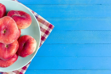 Healthy organic food, Red nectarines on a plate and blue wooden background. Stock Photo