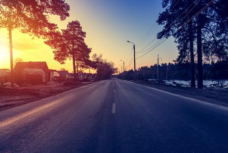 Carretera asfaltada al amanecer y al sol.