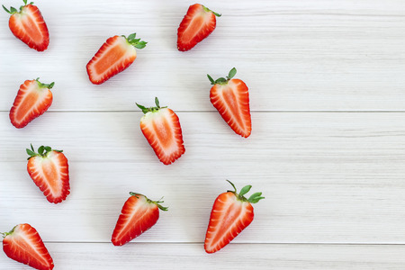 Strawberry fruits on the left side on wooden background.Top view