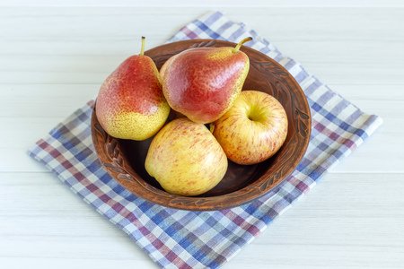 Red pears and apple in brown plate on white wooden table