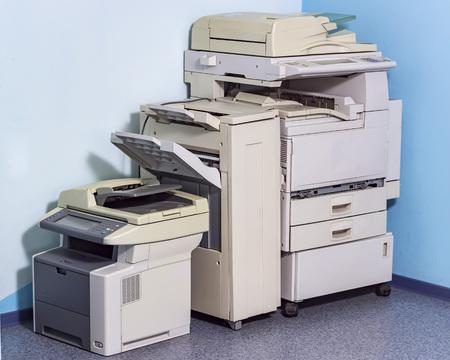Old broken office equipment stands on the floor in the corner