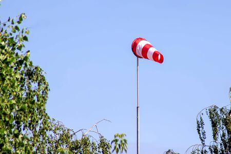 Windsock indicating wind on blue sky background 스톡 콘텐츠