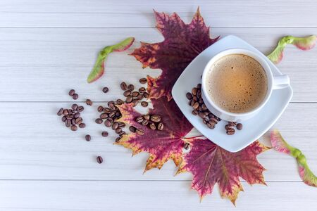 Coffee in cup and coffee beans, isolated spread on a white background with autumn red leaves