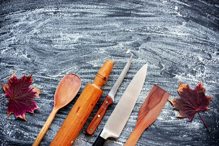 Various wooden old kitchen utensils on a dark background with sprinkled flour. Stock Photo