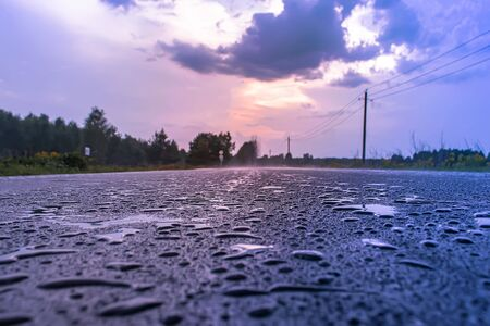Paved road with raindrops at sunset in purple tone.