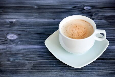 Black coffee in the white cup on the dark wooden background. Stock Photo
