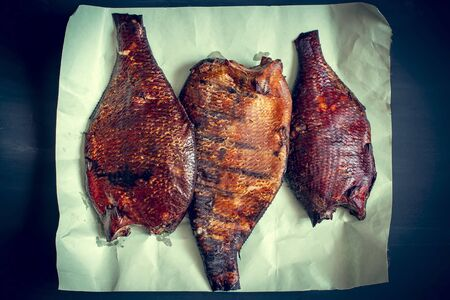 Golden smoked breams on paper. Dark background. Top view