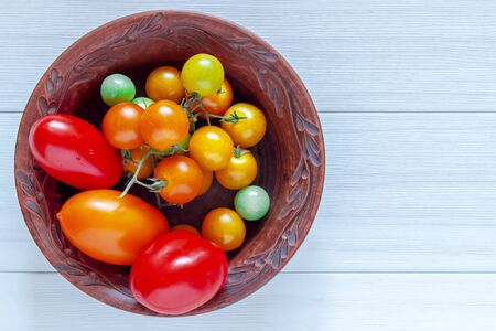 Red, ripe tomatoes in a plate on a white background. Harvesting tomatoes. Top view