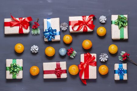Christmas gift box on a dark background and tangerines. New Years attributes