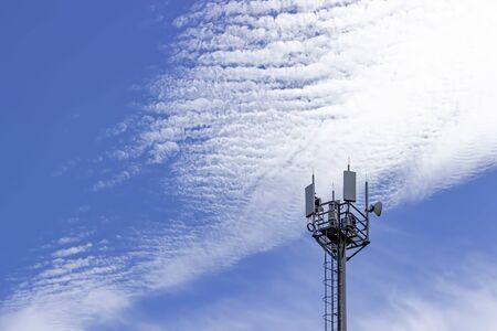 Cell tower on a background of blue sky and clouds. Communication technology. Telecommunication industry. Mobile or telecom network