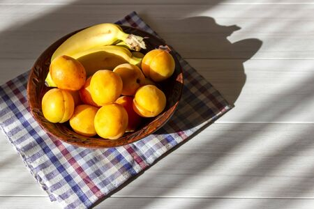 Bananas and apricots lie in a plate on a white table Stok Fotoğraf - 132092762