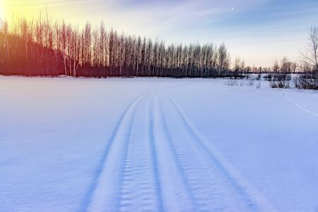 Snowmobile track in snowlandscape. Winter time background