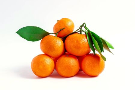 Tangerines or clementines with green leaf isolated on white background