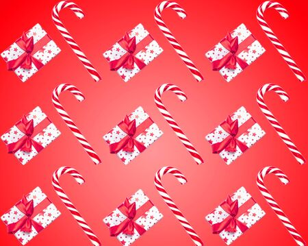 Pattern made from Christmas candy canes and gifts isolated on red background. Christmas holiday concept. 版權商用圖片