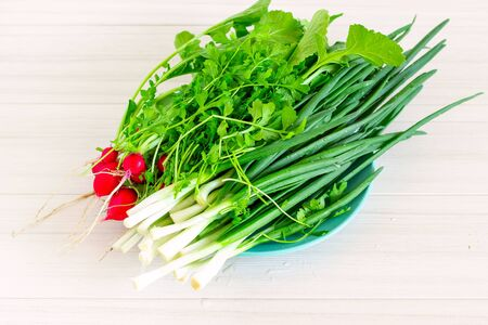 Fresh radish and chives on white table. Health food