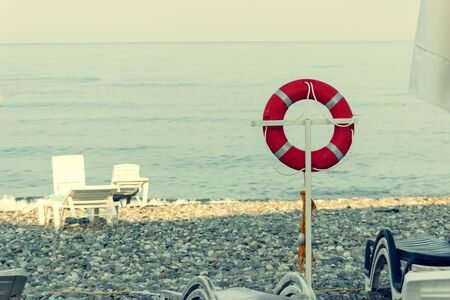 Life buoy on a pole on a beach with blue ocean water