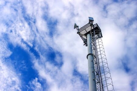 Cell tower transmitting signals of mobile phone and Internet against the blue sky. Bottom view
