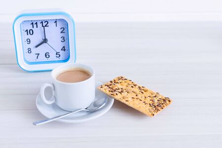 Cup of coffee with cereal cookies on a white wooden table. Breakfast time 版權商用圖片