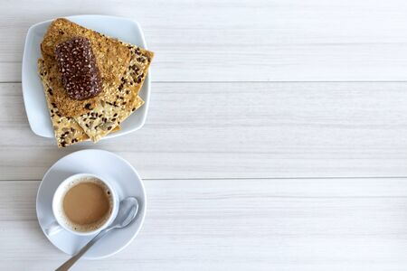 Cup of coffee with cereal cookies on a white wooden table. Breakfast time 스톡 콘텐츠