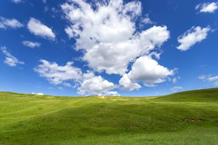 Green hills against the blue sky with clouds. Beautiful screensaver Stock Photo