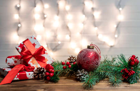 Christmas decoration with spruce branches with a red ball and a garland. Winter holiday light decoration.
