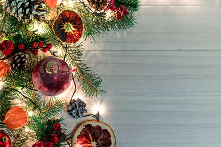 Christmas decoration with spruce branches with a red ball and a garland. Winter holiday light decoration. Top view.