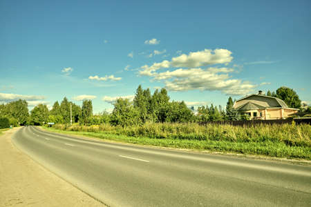 Asphalt road among hills and green grass