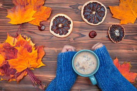 Autumn flat lay. Female hands with cup of coffee, over colorful maple leaves background. Top view. Season concept