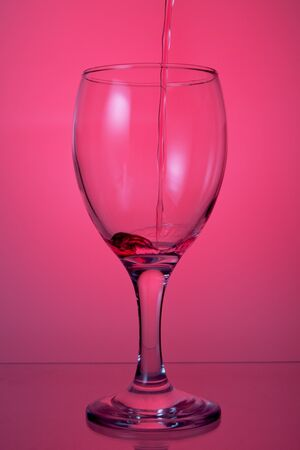 pouring wine into a glass on a pink background. photo
