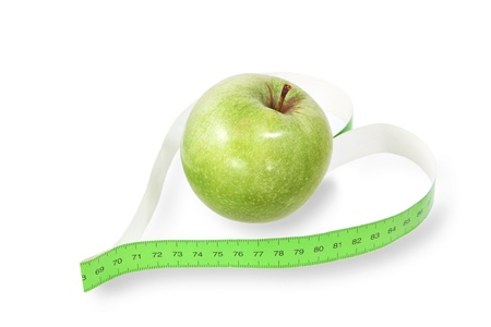 Measuring tape a heart-shaped with a green apple photo