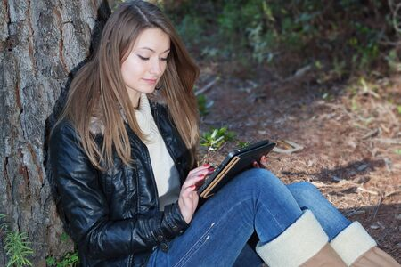 A girl enjoys the tablet, in nature. photo
