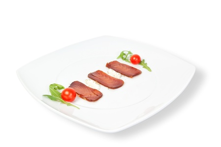 The composition of smoked tuna on a plate. On a white background. photo