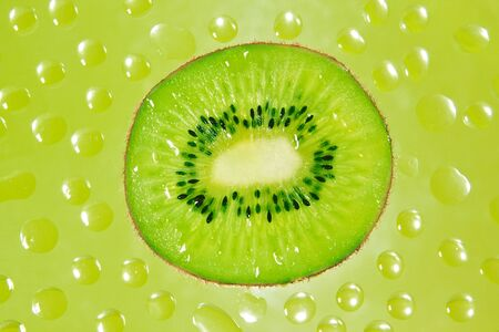 A fresh slice of kiwi fruit in green background drops  photo