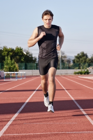 A young man run a hundred meters on the treadmill  photo
