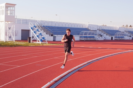 A young man run jogging in the stadium  photo