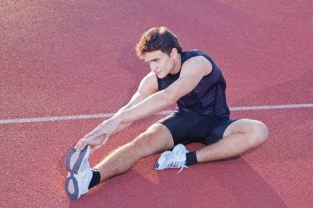 Athlete stretching after jogging in the stadium  photo